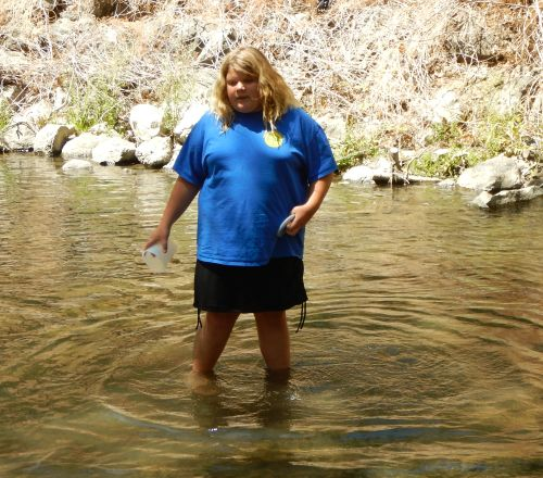 Granddaughter hunts live fish at the local creek