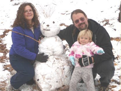 Dawn, John and Kara Siemer with a snowman.
